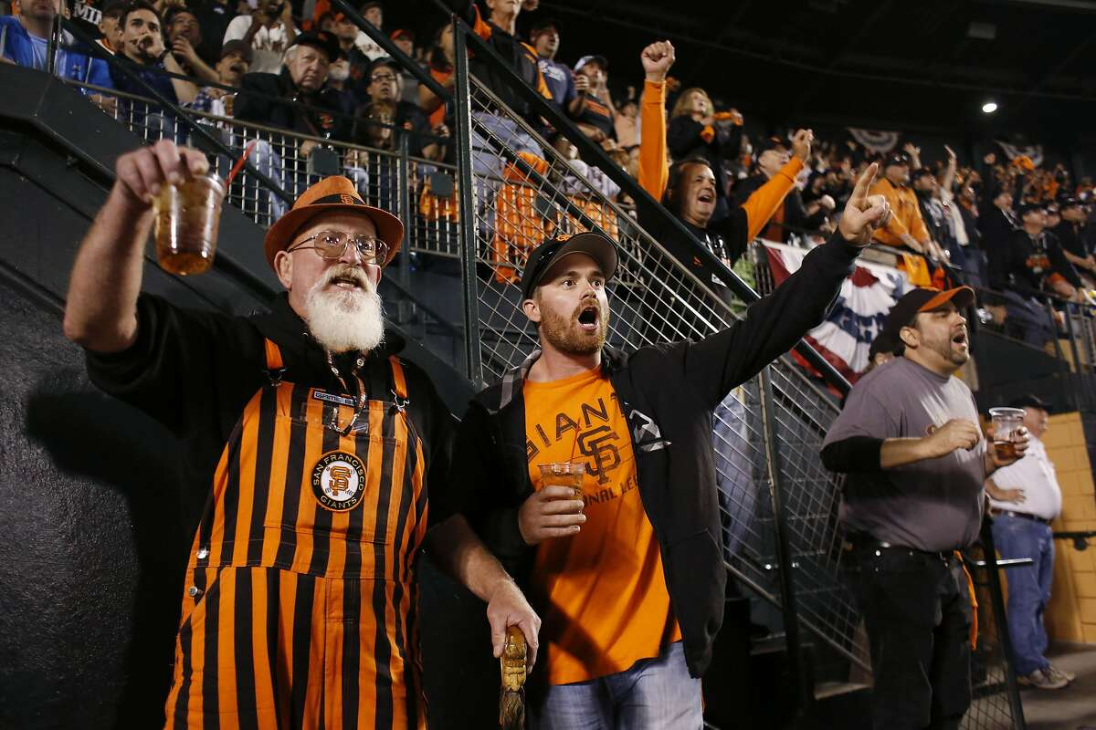 Giants fans Scott Pace and his son Zack Pace of Newark, Calif., react prematurely as Pablo Sandoval makes contact during the 5th inning of game five of the World Series against the Kansas City Royals at AT&T Park on Sunday Oct. 26, 2014 in San Francisco, Calf.