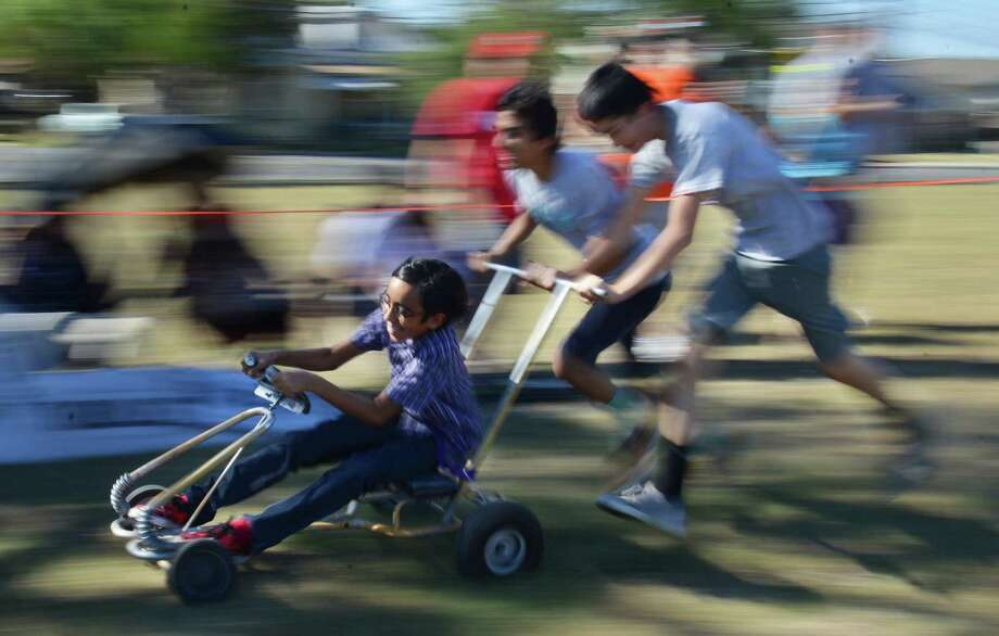 Matteo Tristan (from left), Marcus Bernao and Joaquin Ortiz cross the finish line at the Dignowity Hill Pushcart Derby. Photo: Photos By Matthew Busch / For The San Antonio Express-News / © San Antonio Express-News