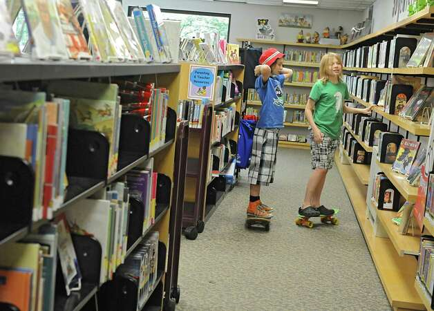 Sasha Holden, 13, and Vanya Holden, 11, of Albany stand on their skateboards as they check the books out at the Albany Public Library Tuesday, June 17, 2014 in Albany, N.Y. An initiative for children to offer the APL MyCard was announced by Albany Public Library, Albany Mayor Kathy Sheehan and the City School District.  (Lori Van Buren / Times Union) Photo: Lori Van Buren / 00027391A