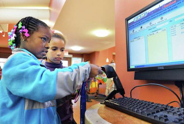 """Demmiko Babb, 7, left, and Juliana Blake,8, use a """"MyCARD"""" library card to log in for computer time at the Delaware branch of the Albany Public Library Thursday Oct. 9, 2014, in Albany, NY.  (John Carl D'Annibale / Times Union) Photo: John Carl D'Annibale / 10028956A"""