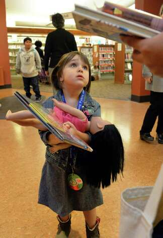 """Wearing her """"MyCARD"""" library card, 4-year-old Coral Padfield asks her mother about taking out a book at the Delaware branch of the Albany Public Library Thursday Oct. 9, 2014, in Albany, NY.  (John Carl D'Annibale / Times Union) Photo: John Carl D'Annibale / 10028956A"""