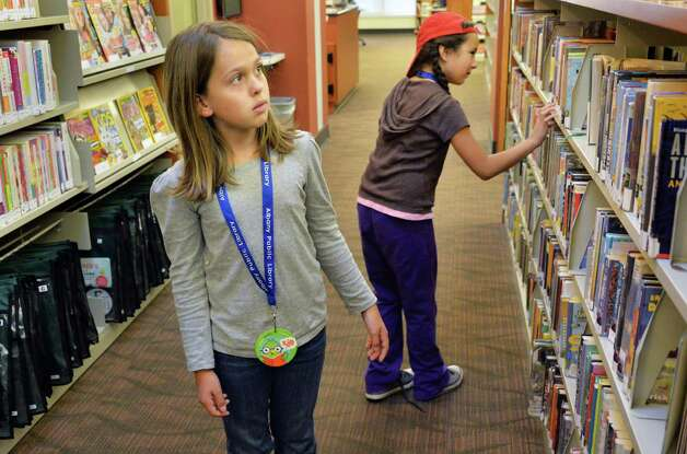 """Wearing their """"MyCARD"""" library  cards, Lila Padfield,9, left, and Julia Davis, 8, choose books to take out at the Delaware branch of the Albany Public Library after school Thursday Oct. 9, 2014, in Albany, NY.  (John Carl D'Annibale / Times Union) Photo: John Carl D'Annibale / 10028956A"""