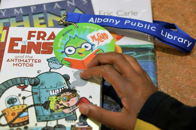 """The new """"MyCARD"""" library card allows kids to take out three books at a time and they do not have to pay fines for late books at the Albany Public Library Thursday Oct. 9, 2014, in Albany, NY.  (John Carl D'Annibale / Times Union) Photo: John Carl D'Annibale / 10028956A"""