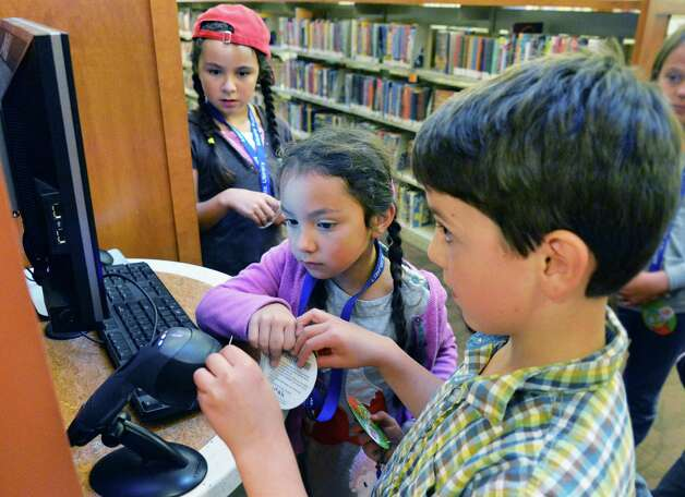 """Julia Davis, 8, left, Sarah Davis, 5, and Liam Padfield, 7, right, use a """"MyCARD"""" library card to log onto a computer at the Delaware branch of the Albany Public Library after school Thursday Oct. 9, 2014, in Albany, NY.  (John Carl D'Annibale / Times Union) Photo: John Carl D'Annibale / 10028956A"""