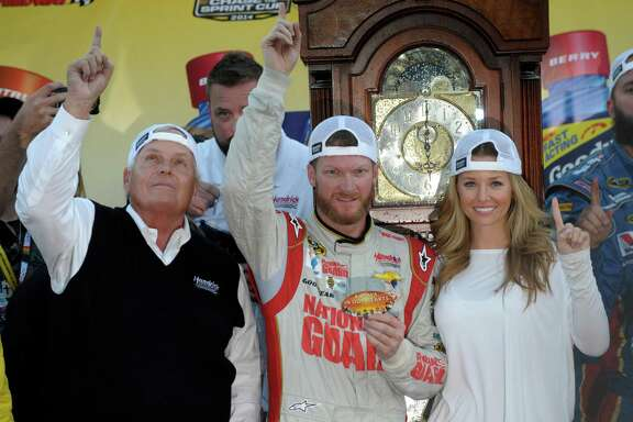 Dale Earnhardt Jr., center, and his girlfriend Amy Reimann, right, and team owner, Rick Hendrick, left, celebrate after Earnhardt won the NASCAR Sprint Cup Series auto race at Martinsville Speedway in Martinsville, Va., Sunday, Oct. 26, 2014. The grandfather clock, background, is the winner's trophy. (AP Photo/Don Petersen)