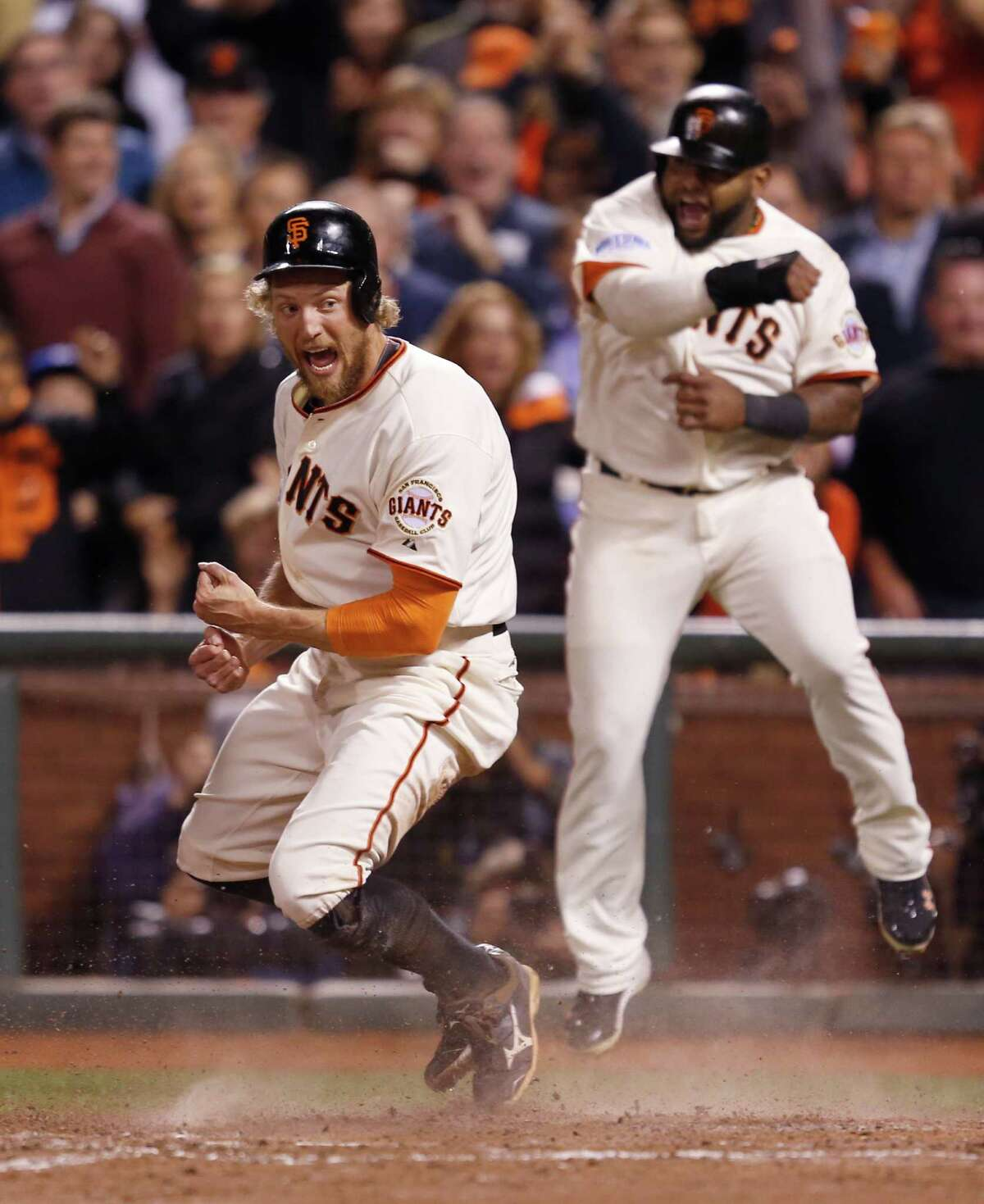 Giants Hunter Pence and Giants Pablo Sandoval celebrate their eighth inning score off a Juan Perez triple during Game 5 of the World Series at AT&T Park on Sunday, Oct. 26, 2014 in San Francisco, Calif.
