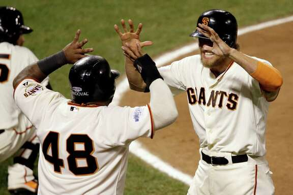San Francisco Giants' Pablo Sandoval (48) and Hunter Pence celebrate after scoring on a double by Juan Perez during the eighth inning of Game 5 of baseball's World Series against the Kansas City Royals Sunday, Oct. 26, 2014, in San Francisco. (AP Photo/Eric Risberg)