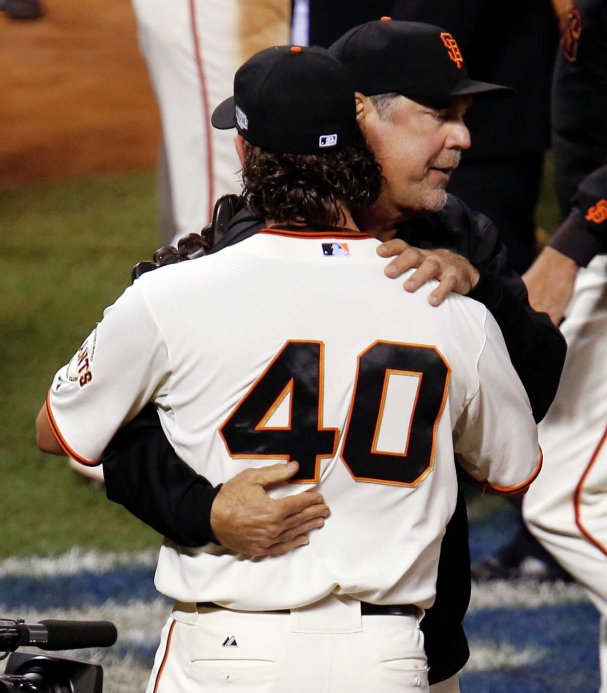 Giants manager Bruce Bochy congratulates Madison Bumgarner after the Giants win game five of the World Series at AT&T Park in San Francisco, California, on Sunday Oct. 26, 2014.