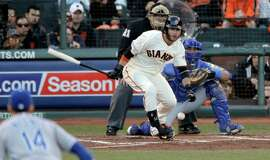 Giants shortstop Brandon Crawford hits a groundball to second base, allowing Hunter Pence to score the first run of Game 5 in the second inning.