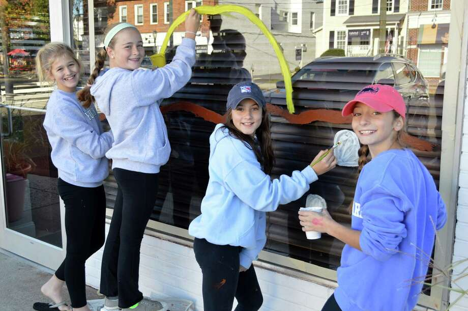 Peyton Rooney, 11, Quincy Balanoff, 12, Sophia Talwalker, 12, and Mackenzie Swift, 12, apinted a Halloween scene on UCBC's window on Saturday. Photo: Jarret Liotta / Darien News