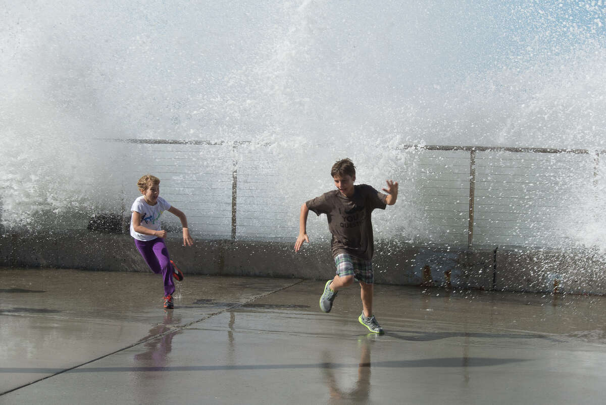 PLAYING CHICKEN WITH THE OCEAN: Kids scatter as a wave crashes against the seawall during a day of high surf in Rockaway Beach, Pacifica.
