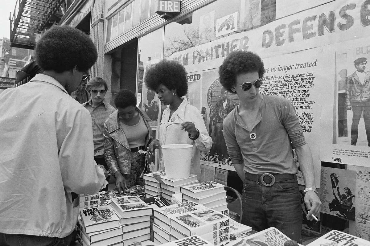 An unidentified man and woman stand behind a sales table full of Black Panther Party literature and buttons in front of the organization's office in New Haven, Connecticut, in May 1970. Visible are copies of Bobby Seale's