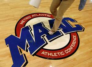 Times Union staff photo by Cindy Schultz -- MAAC employee Evangelia Papamarkou (cq) walks over the MAAC sticker on the arena floor on Wednesday, March 1, 2006, at the Pepsi Arena in Albany, N.Y.