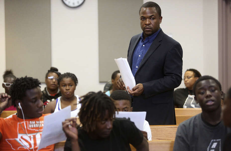 Taj Matthews, president and CEO of the Claude & ZerNona Black Developmental Leadership Foundation, watches over the teens as they wait for their mock trial to begin. Photo: Photos By Lisa Krantz / San Antonio Express-News / SAN ANTONIO EXPRESS-NEWS