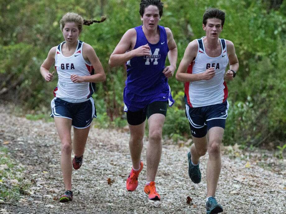 GFA Junior Maggie Boudreau (Wilton), right, and sophomore Scott Barnet (Ridgefield) team up against a Masters runner (and inclement weather) to the finish at the Brunswick School meet on Wednesday, Oct. 22. Photo: Contributed Photo / Westport News Contributed
