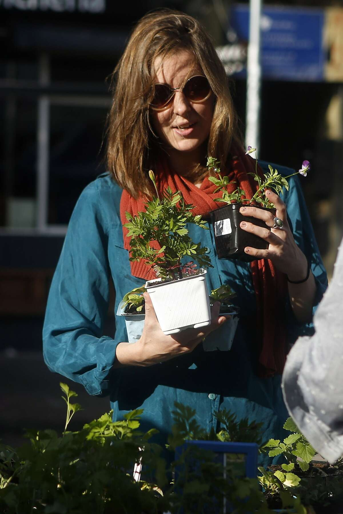 Jennifer Kindell buys plants from the Urban Sprouts program at a farmer's market on 22nd Street in San Francisco, Calif. on Thursday, October 9, 2014.