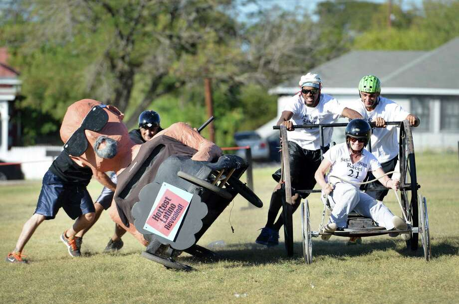 Team More Brains Than Hair (left) nearly tips over on a turn as team Bexar County nudges past them during the official Dignowity Hill Pushcart Derby. More than 100 spectators took in the annual event. Photo: Matthew Busch / For The San Antonio Express-News / © San Antonio Express-News