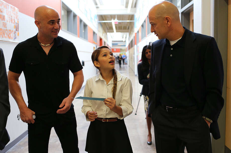 Seventh-grader Amanda Abeja, 13, center, explains a student paycheck to former professional tennis player Andre Agassi (left) and philanthropist Bobby Turner during a tour and ribbon cutting ceremony of the KIPP San Antonio Commerce Campus. Photo: Jerry Lara / San Antonio Express-News / © 2014 San Antonio Express-News