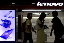 FILE - In this Aug. 15, 2013 file photo, people walk past a Lenovo flagship experience store in Beijing, China. Lenovo Group has received U.S. and European approval to complete its acquisition of IBM Corp.'s low-end server business and plans to use it to grow faster outside its personal computer business, Lenovo's chairman said Monday, Sept. 29, 2014. (AP Photo/Andy Wong, File)
