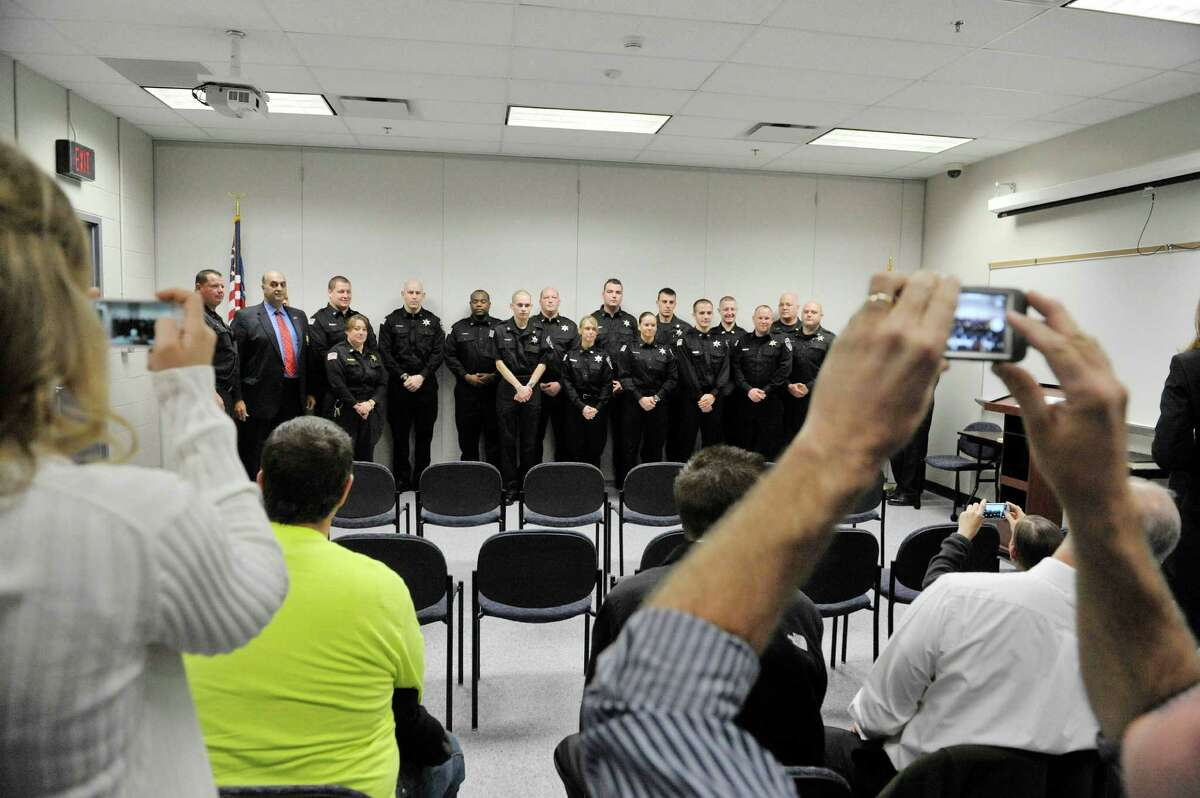 Family and friends take photographs at a ceremony where 12 new correctional officer were sworn in at the Rensselaer County Jail on Monday, Oct. 27, 2014, in Troy, N.Y. In the photo the newly sworn in officers pose with current officers and jail officials. (Paul Buckowski / Times Union)