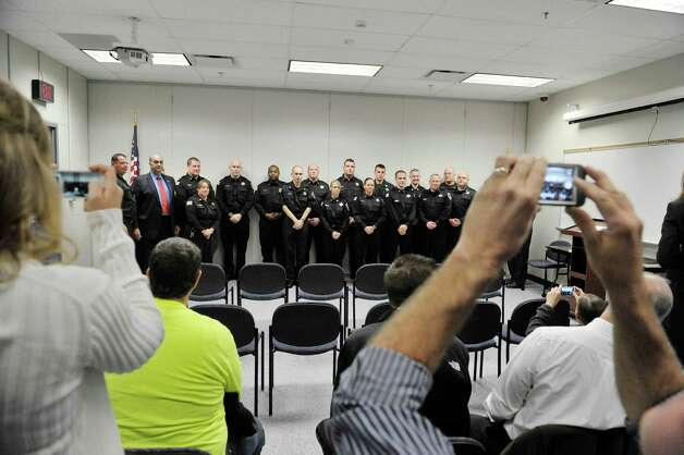 Family and friends take photographs at a ceremony where 12 new correctional officer were sworn in at the Rensselaer County Jail on Monday, Oct. 27, 2014, in Troy, N.Y.  In the photo the newly sworn in officers pose with current officers and jail officials.  (Paul Buckowski / Times Union) Photo: Paul Buckowski / 00029175A