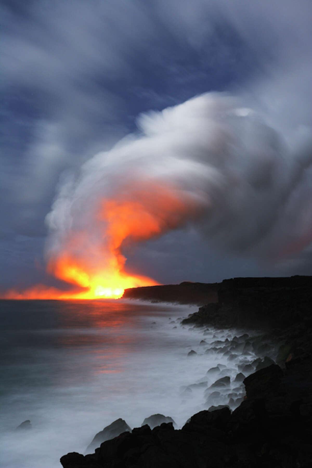 Smoke is reflecting lava light under moonlight.