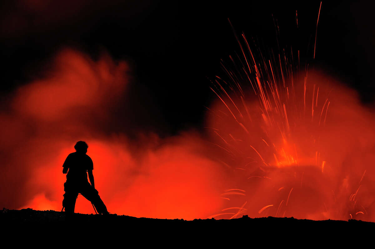 Woman watching lava eruption on crater edge