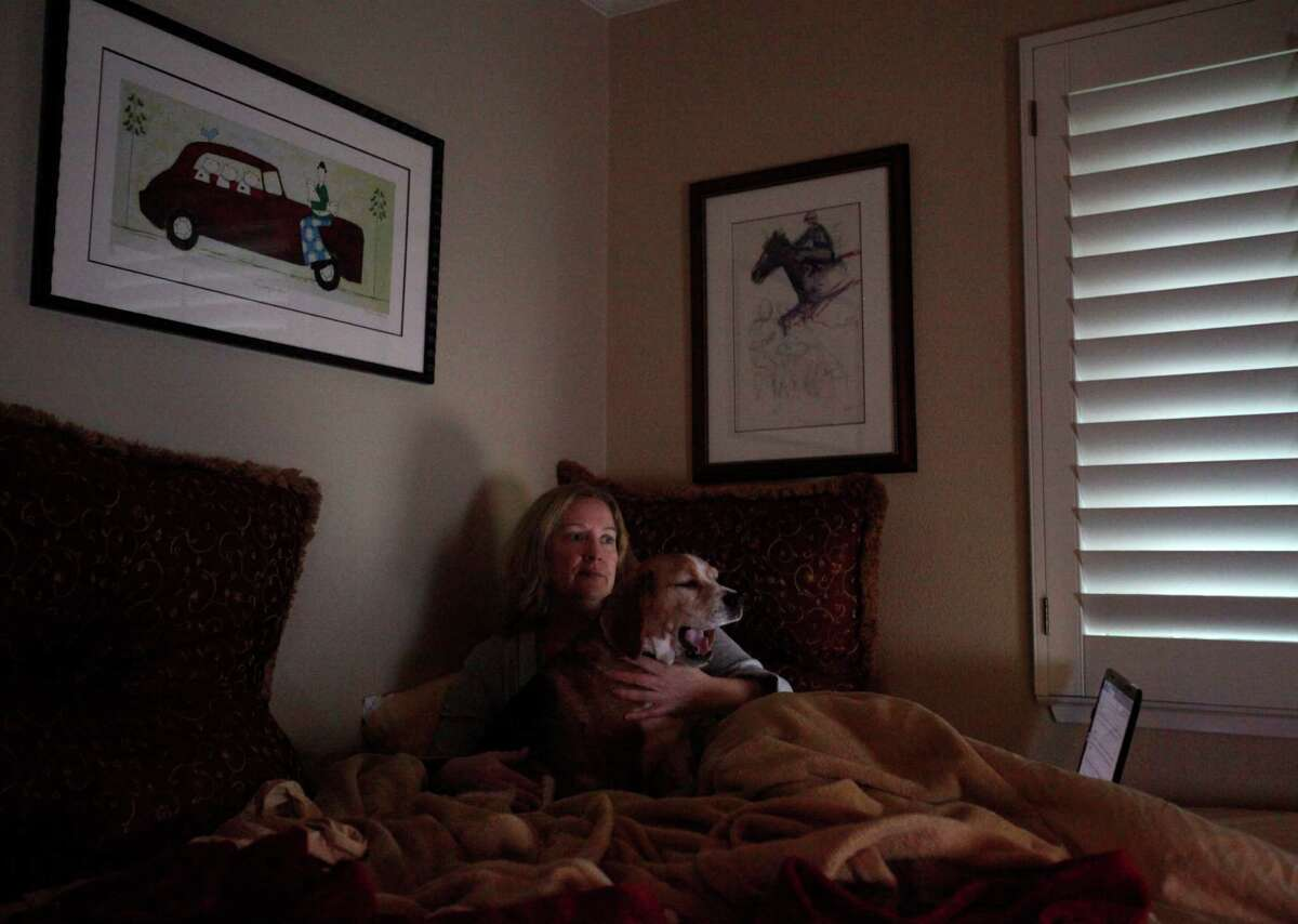 Susan Kreutzer watches television with her dog Rusty in her Danville home. She has been mostly bedridden since her chronicle fatigue flared up again in April.