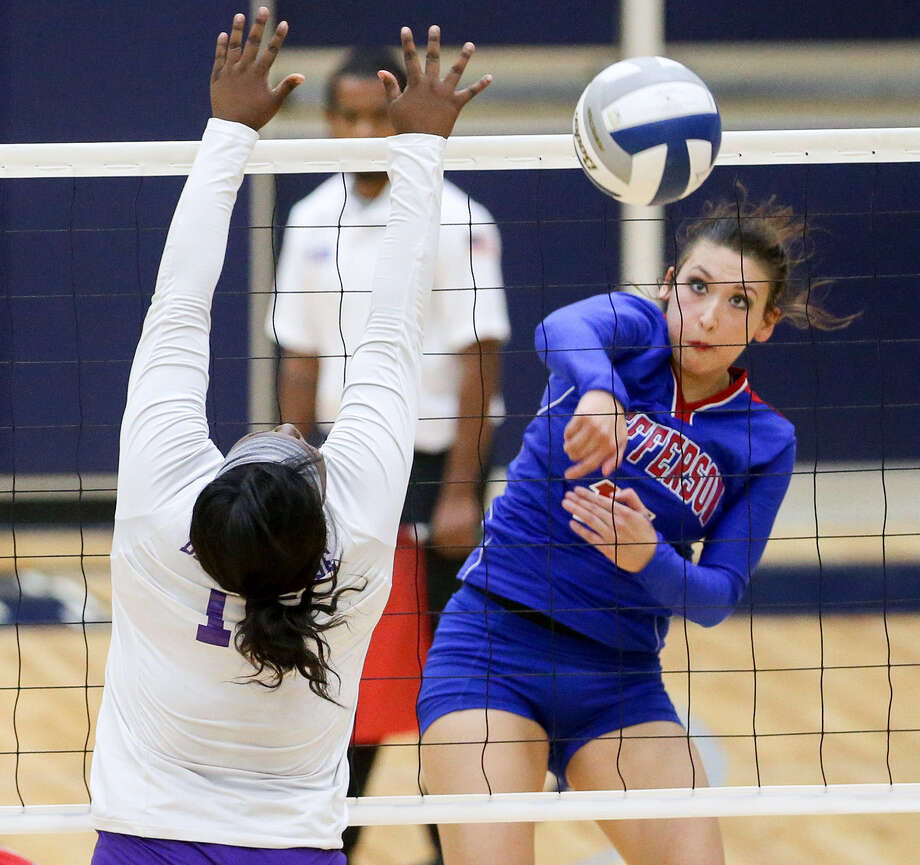 Jefferson's Gabriella Vasquez (right) gets a kill shot past Brackenridge's Marquanique Freeman during their match Oct. 21. Brackenridge beat the Lady Mustangs in five sets. Photo: Marvin Pfeiffer / EN Communities / EN Communities 2014