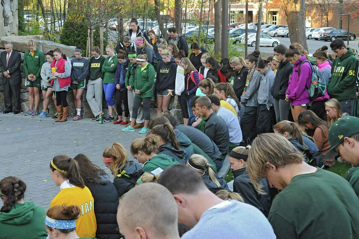 Siena athletes bow their heads as Rev. Larry Anderson presides over the annual