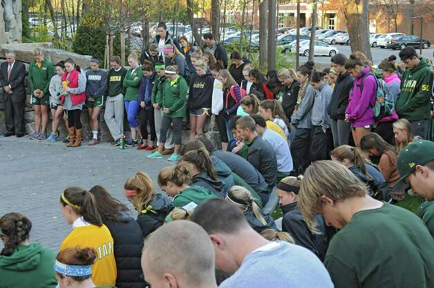 """Siena athletes bow their heads as Rev. Larry Anderson presides over the annual """"Blessing of the Athletes""""  ceremony  at The Grotto at Siena College on Monday, Oct. 27, 2014 in Loudonville, N.Y. (Lori Van Buren / Times Union) Photo: Lori Van Buren / 00029221A"""