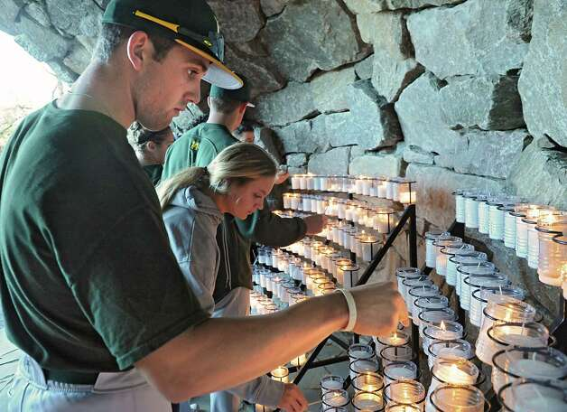 """Siena junior baseball player Alex Tuccio of Ridgefield, Conn., lights a candle for his late father after Rev. Larry Anderson presided over the annual """"Blessing of the Athletes""""  ceremony  at Siena College on Monday, Oct. 27, 2014 in Loudonville, N.Y. The ceremony took place at The Grotto, modeled after the shrine in Lourdes, France. Siena's grotto incorporates the spirit of the original with a miniature stream and candles sheltered under a stone arch. (Lori Van Buren / Times Union) Photo: Lori Van Buren / 00029221A"""