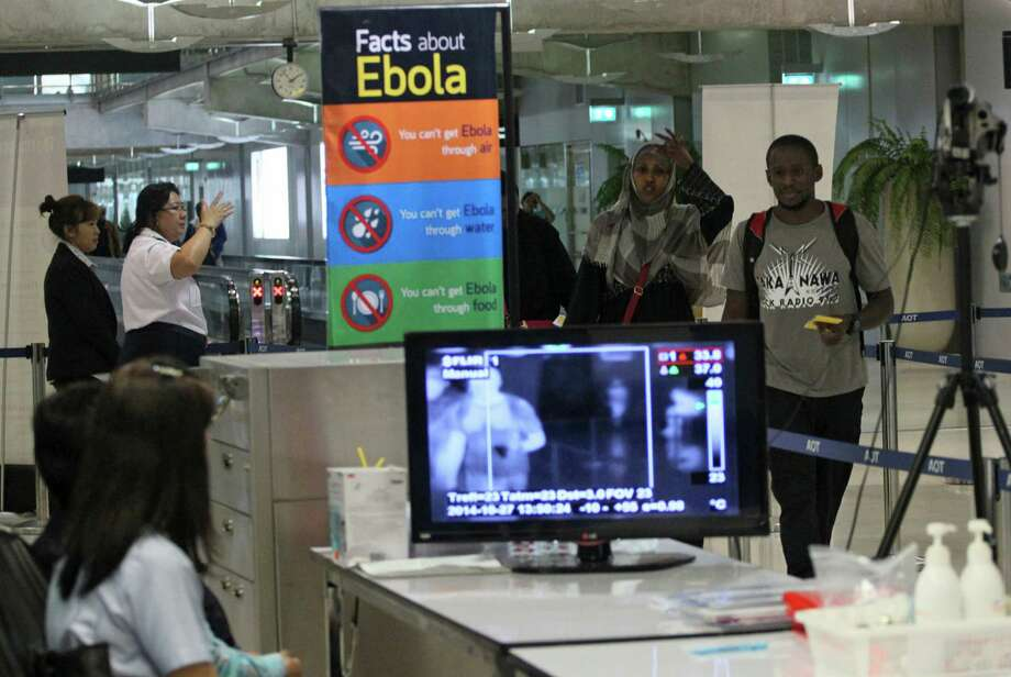Tourists pass through a thermal scanner at Suvarnbhumi Airport in Bangkok, Thailand after arriving from Ethiopia. Thermal Scans are set in the airport for screening infectious diseases, including Ebola. The virus is creating challenges for publci officials around the globe. Photo: Sakchai Lalit / Sakchai Lalit / Associated Press / AP