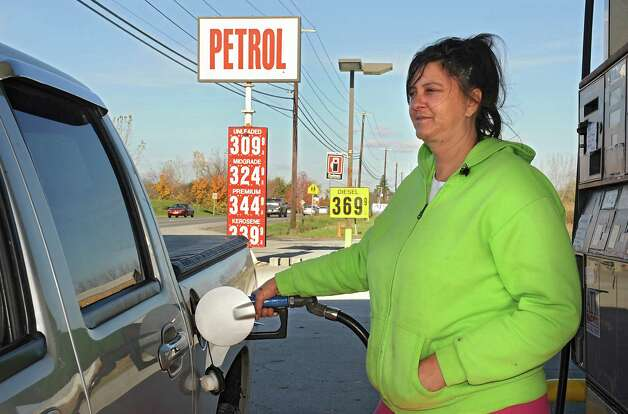 Delisia Brink of Durham was happy with the price of $3.09 a gallon for regular gas at the Petrol gas station on 9W Monday, Oct. 27, 2014, in Glenmont, N.Y. (Lori Van Buren / Times Union) Photo: Lori Van Buren / 00029215A
