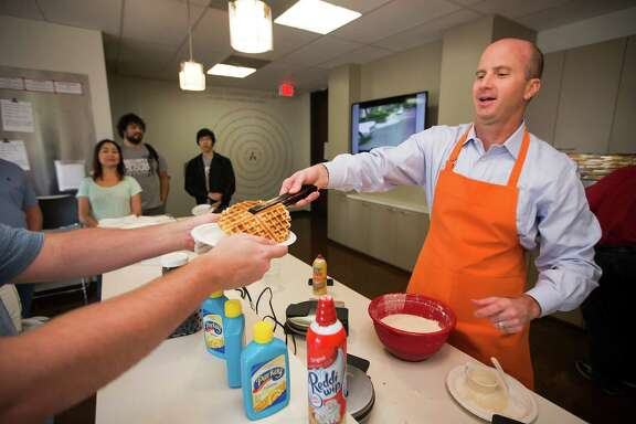 "Alert Logic CEO Gray Hall serves waffles to his employees during ""Waffle Wednesday"" at the cyber security firm on Wednesday, Oct. 8, 2014, in Houston.  Once a month Alert Logic executives cook waffles for their employees."