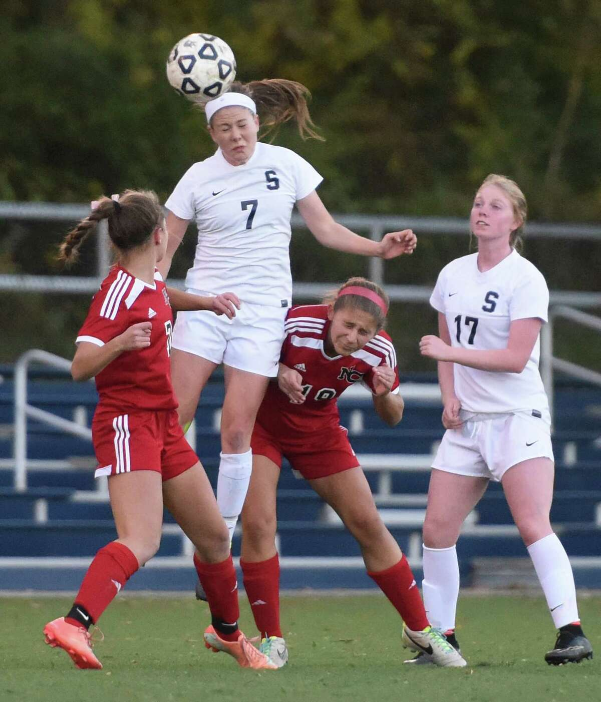 Staples' Chloe Rosenfield (7) goes up for a header against New Canaan defenders Abigail Farley, left, and Katharine Kuchinski as teammate Margaret Walsh (17) watches from behind in No. 4 Staples' 4-0 win over No. 8 New Canaan in the FCIAC high school girls soccer semifinal game at Wilton High School in Wilton, Conn. Monday, Oct. 27, 2014.