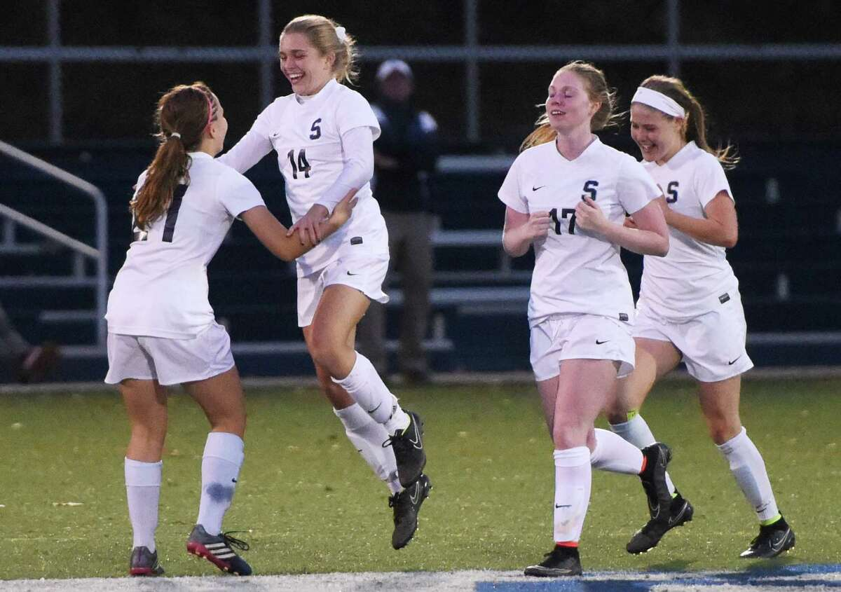 Staples' Lydia Shaw (14) celebrates her goal with teammates Adelaide Fowle (21), Margaret Walsh (17) and Chloe Rosenfield (7) in No. 4 Staples' 4-0 win over No. 8 New Canaan in the FCIAC high school girls soccer semifinal game at Wilton High School in Wilton, Conn. Monday, Oct. 27, 2014.