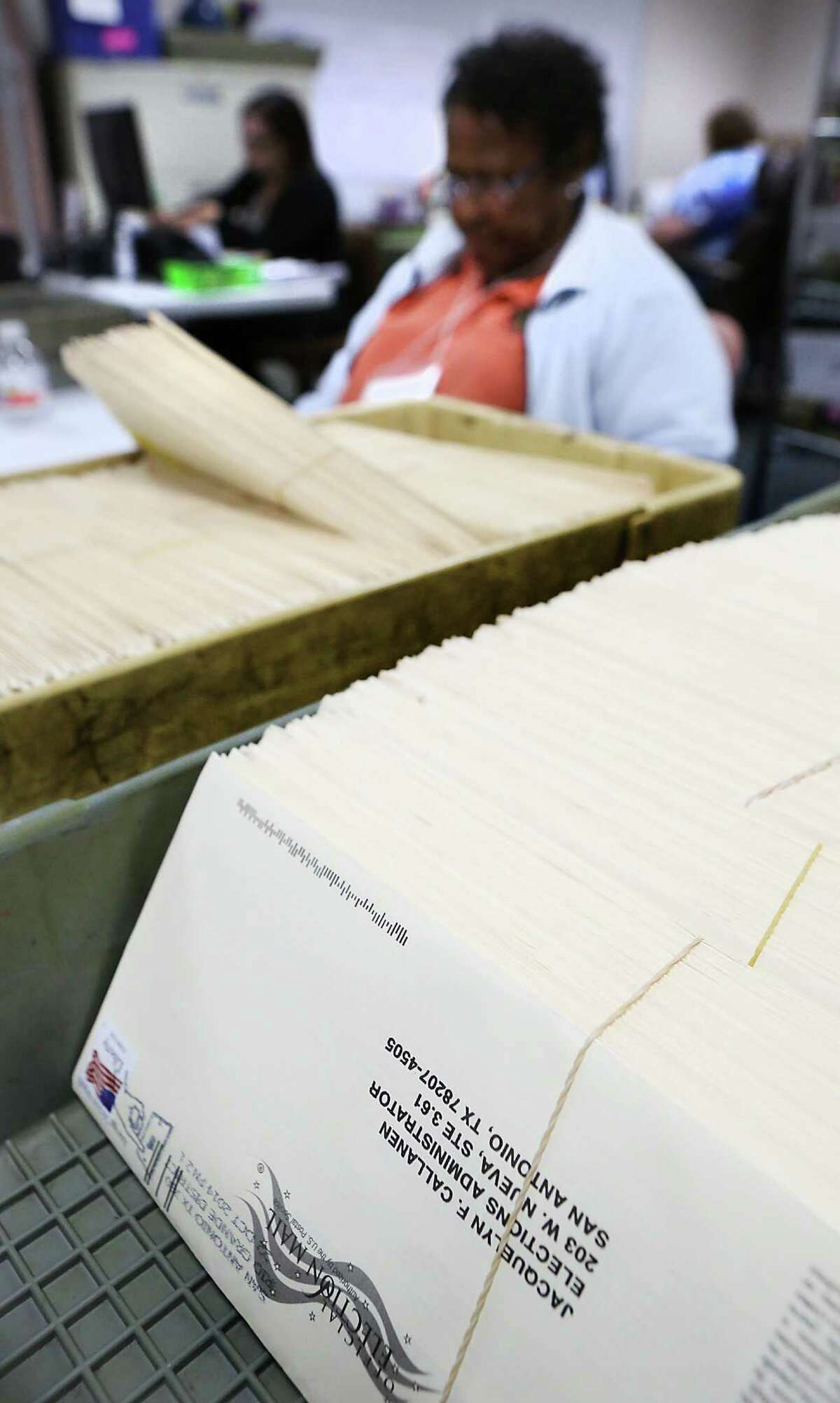 Workers at the Bexar County Elections Department sort through mailed in election ballots making sure they are signed. Thursday Oct. 23, 2014.