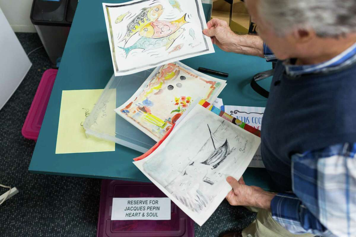 Before taping his cooking show for KQED, chef Jacques Pepin looks over some of his paintings to be used in a children's cookbook.