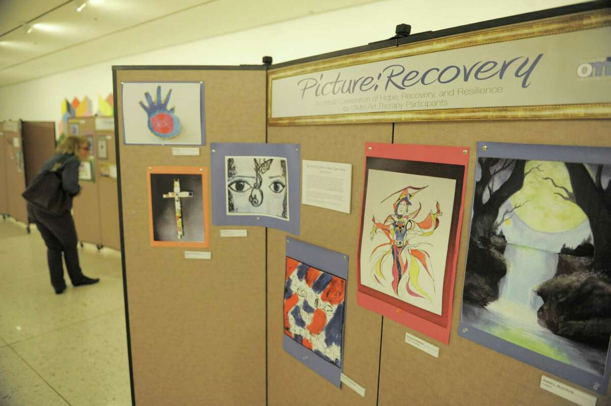 Visitors look over the work at the Recovery Art Show opening at the South Concourse of the Empire State Plaza on Monday, Oct. 27, 2014, in Albany, N.Y. The Recovery Art Show consists of over 100 pieces of artwork by individuals in recovery from mental illness involved in Office of Mental Health programs throughout New York State. (Paul Buckowski / Times Union)