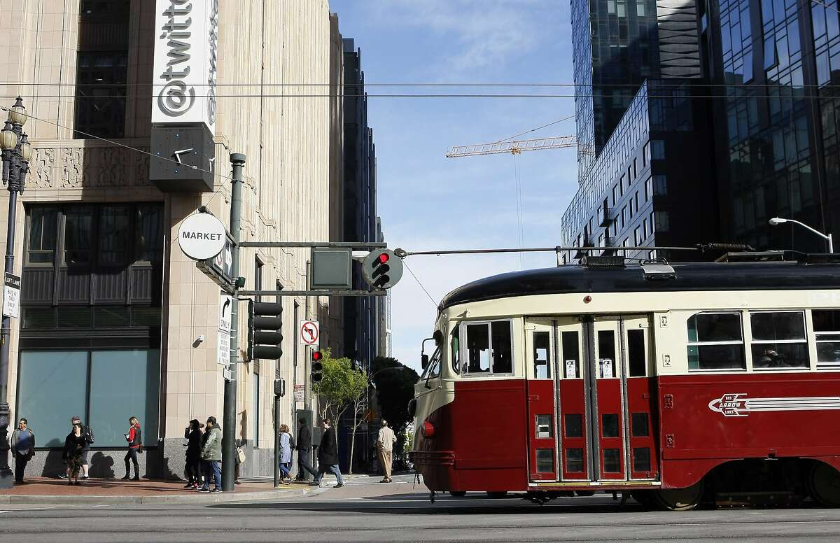 A streetcar passes in front of the Twitter building that was the old Western Furniture Exchange and Merchandise Mart on Market Street on April 25, 2014 in San Francisco, Calif. Tech companies are buying historic buildings within the city thus helping to protect these landmarks.