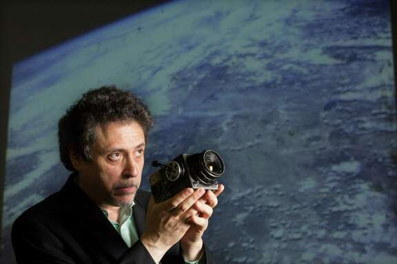Bobby Livingston, with RR Auction, holds the camera that Wally Schirra used to take the first high-quality photographs of Earth from space, including the image projected behind him.