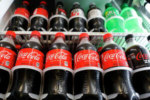 It'd take a 5-mile walk to burn off the calories in a 20-ounce soda.   Bottles of Coca-Cola Co. brand soda are displayed for sale at a convenience store in Redondo Beach, California, U.S., on Monday, July 15, 2013. The Coca-Cola Co. is scheduled to release earnings data on July 16. Photographer: Patrick Fallon/Bloomberg