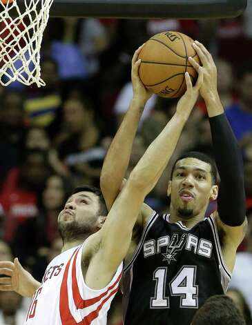 San Antonio Spurs' Danny Green (14) grabs a rebound over Houston Rockets' Kostas Papanikolaou (16) during the second half of an NBA exhibition basketball game Friday, Oct. 24, 2014, in Houston. The Rockets won 96-87. (AP Photo/Pat Sullivan) ORG XMIT: HTR116 Photo: Pat Sullivan / AP
