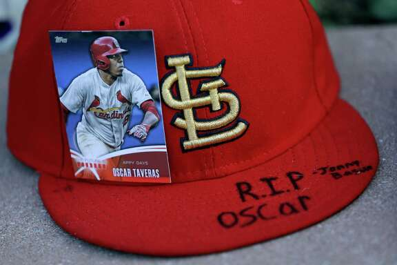 An Oscar Taveras baseball card is attached to a hat as part of a makeshift memorial outside Busch Stadium in St. Louis on Monday.