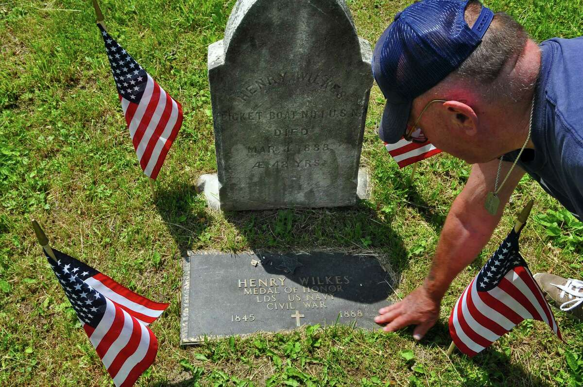In this 2011 archive image, Charles Stock of Rensselaer wipes away grass from the grave of Henry Wilkes, who was awarded the Medal of Honor for his actions with US Navy during the Civil War in 1864. Wilkes is buried in Beverwyck Cemetery in Rensselaer. ( Philip Kamrass / Times Union archive)