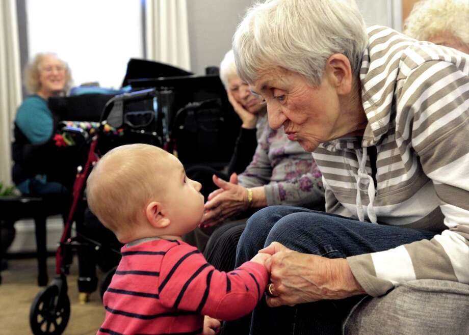 """Mary Mayfield grabs the attention of Mason Zeigler, 7 months, of Danbury, during """"Music, Memory and Connection"""", an intergenerational music class that involves residents and children, at Maplewood at Danbury, a senior living facility, in Danbury, Conn. Saturday, October 25, 2014. Photo: H John Voorhees III / The News-Times Staff Photographer"""