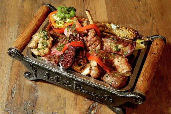 The parillada , a grilled meats assortment on a sort of wood-and-cast iron barge with a splash of color from a stuffed pepper.at Sal Y Pimienta, South American Cuisine restaurant in Houston, TX. (PhotoFor the Chronicle by Thomas B. Shea)