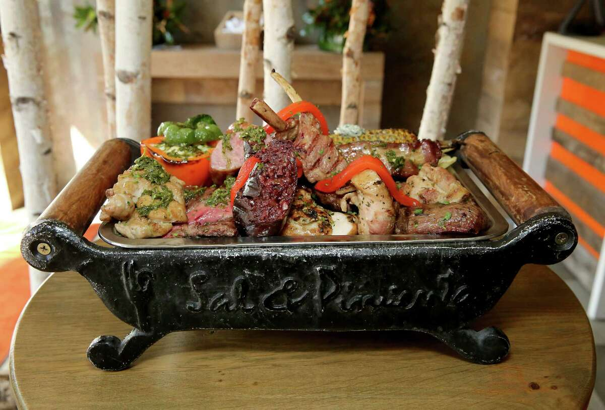 The parillada, a grilled meats assortment on a sort of wood-and-cast iron barge with a splash of color from a stuffed pepper at Sal Y Pimienta, South American Cuisine restaurant.