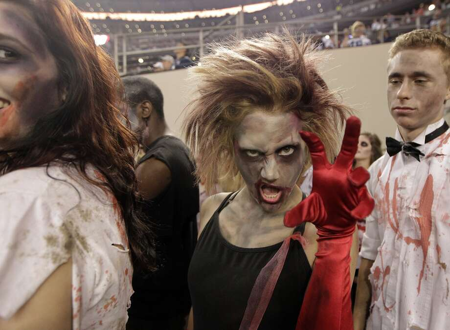 "DALLAS CHEERLEADERS IN DIFFERENT MAKEUP: Dallas Cowboys cheerleaders and guests prepare to perform during a Halloween-themed half time of the ""Monday Night Football"" game against Washington in Arlington, Texas. Photo: Tim Sharp, Associated Press"